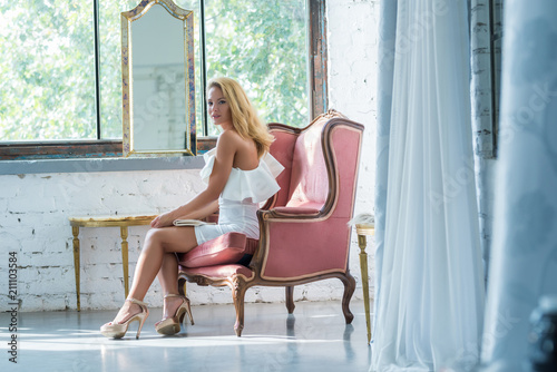 Obraz na plátne Portrait of a beautiful young woman sitting in a antique armchair