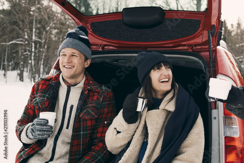 Friends sitting in back of car drinking coffee