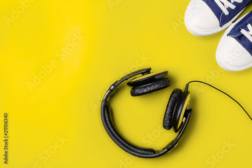 Fotografía  A pair of new stylish sneakers and headphones on a yellow bright background