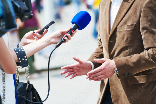 Fototapeta media reporter with microphone making journalist interview for news obraz