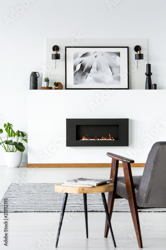 table next to grey armchair in white loft interior with poster abovetable next to grey armchair in white loft interior with poster above black fireplace real photo