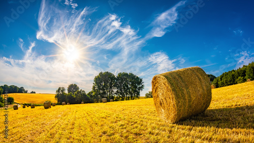 mata magnetyczna Landscape in summer with hay bales on a field and blue sky with bright sun in the background