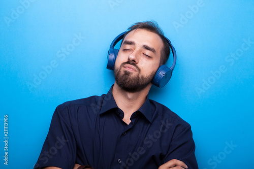 Young man listening to music through headphones on blue background Fototapete
