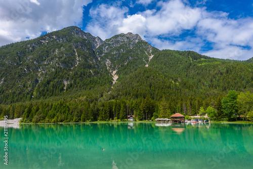 Photo Stands Lake Dobbiaco (Toblacher See, Lago di Dobbiaco) in Dolomite Alps, South Tirol, Italy - Travel destination in Europe
