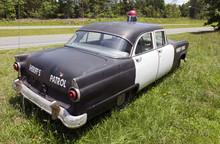Vintage 1950s Sheriff's Patrol Car Parked On Grassy Knoll.