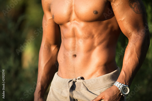 Fotografie, Obraz  Abs and chest closeup of african macho man bodybuilder topless with naked torso