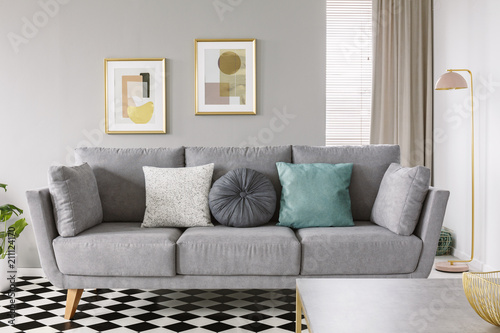 Close Up Of A Gray Sofa With White And Mint Cushions On A Checkered Floor In Classy Living Room Interior With Posters On Gray Wall Real Photo Buy This Stock Photo And