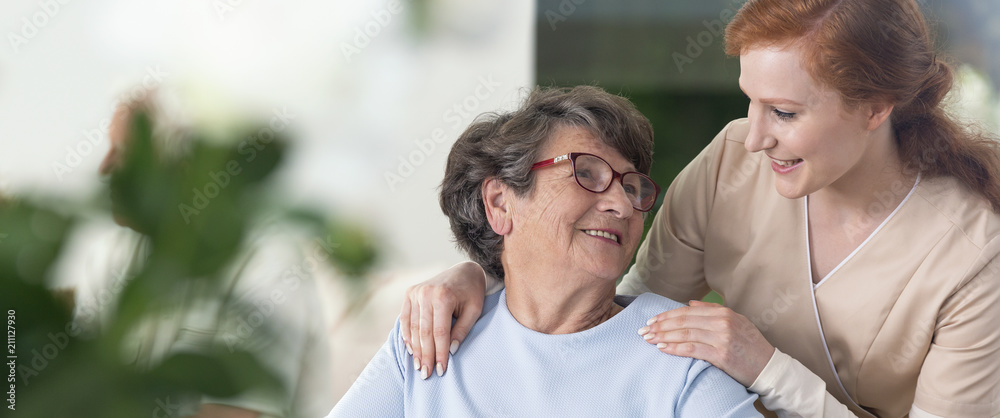 Fototapeta Close-up of a tender caregiver with her hands on the shoulders of a senior woman inside her home. Blurred surrounding. Panorama.