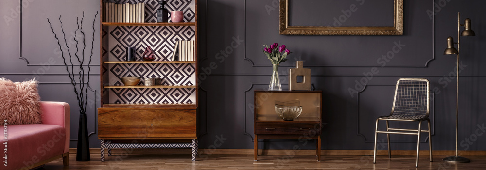 Fototapeta Gold chair standing in dark grey room interior with two vintage wooden cupboards with decor, books and fresh tulips