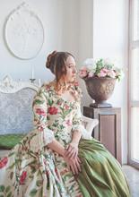 Beautiful Woman In Long Medieval Dress Sitting Near Window