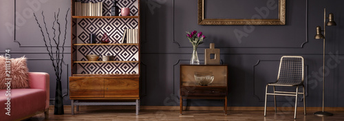 Foto Gold chair standing in dark grey room interior with two vintage wooden cupboards