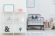 Kid's bedroom interior with a view of one whole bed and a part of the other. Shelves with decorations and posters on the white wall. Real photo