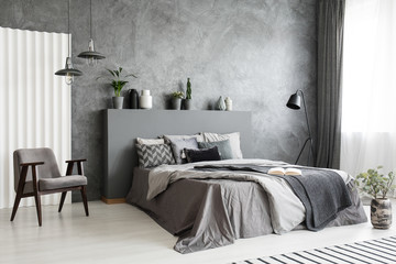 Fototapeta Modern grey bedroom interior with big bed with pillows and linen. Comfortable armchair next to the bed. Real photo.