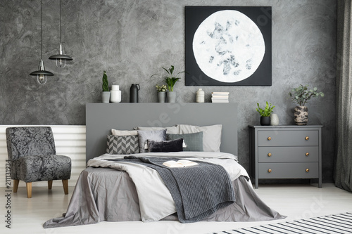 Fototapety, obrazy: Moon art decor on the wall in a stylish grey bedroom interior with a big bed in the middle and an armchair and drawer cabinet besides. Cushions and covers on the bed. Real photo.