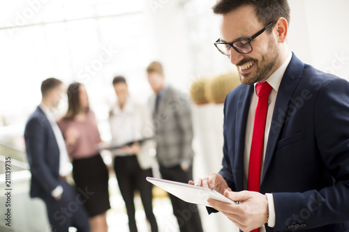 Papiers peints Echelle de hauteur Hardworking businessman dressed in suit standing in modern office and using tablet