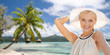 travel, tourism and summer vacation concept - beautiful woman in hat enjoying sun over tropical beach background in french polynesia