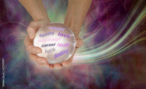 What does the crystal ball say about your future - female hands holding a large clear crystal ball showing various words on an ethereal energy formation background with copy space