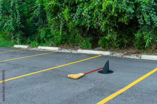 Witch's hat, cape and broom in a parking lot at a local park. Canvas Print