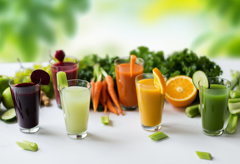 Obraz na Szkle healthy eating, drinks, diet and detox concept - glasses with different fruit or vegetable juices and food on table over green natural background