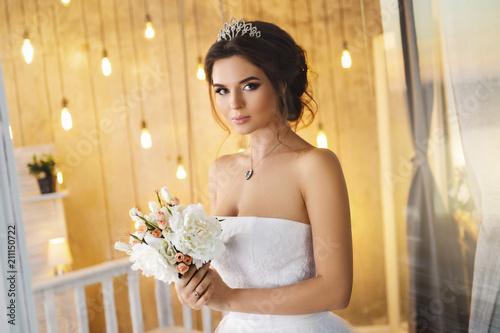 Obraz na płótnie Happy and beautiful bride with bouquet of flowers