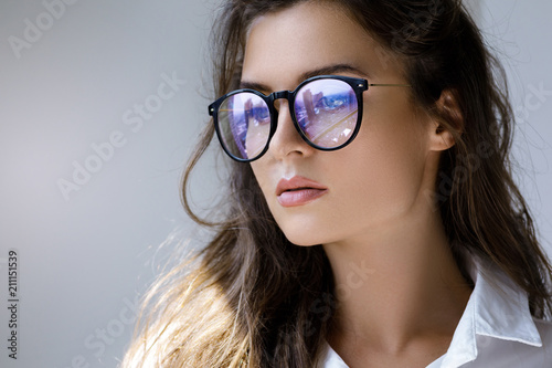 Close up portrait of Young woman with a reflection of modern city inside eyeglas Canvas Print