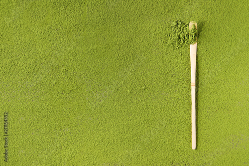 Photo  Green tea matcha powder in traditional bamboo spoon over powdering matcha as background