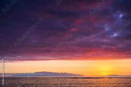 amazing scenic landscape taken during a wonerful sunset on the ocean. La Gomera oceanic island in background with clouds and water in red and orange colors. timeless moment with the sun going down