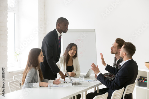 Angry African American worker shouting at Caucasian colleague, blaming for mistake, diverse partners disputing at business meeting, arguing or threatening, showing disrespect Canvas Print
