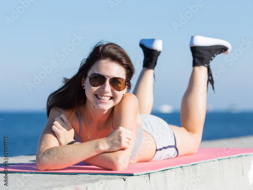 Fotografiet  Sportswoman in sunglasses lying on concrete