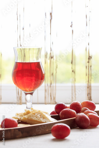 A glass with pink wine, cheese and a bunch of grapes on the background of a white window with a curtain. Light photo