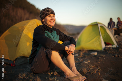 Spoed Foto op Canvas Kamperen Smiling woman sitting near camping tent on beach, Big Flat, Lost Coast Trail, Kings Range National Conservation Area, California, USA