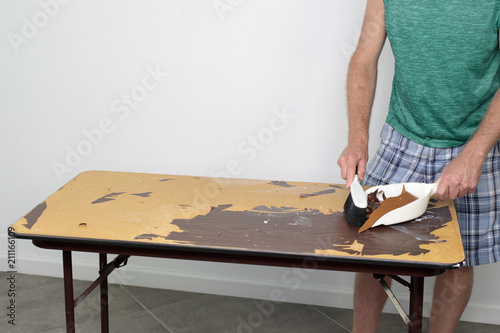 Male Cleans Off Table He Is Preparing To Resurface Sweeping A With