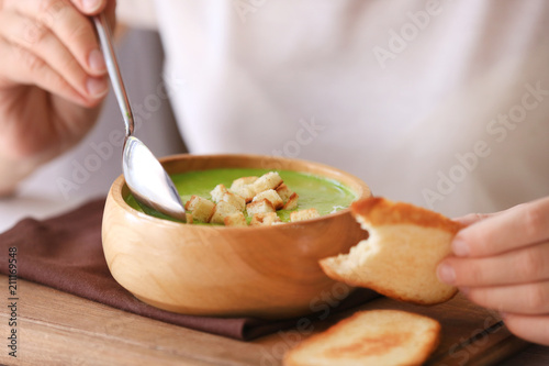 Woman eating tasty spinach soup in kitchen