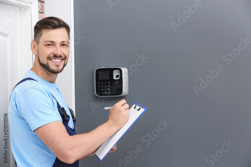 Male technician with clipboard near installed alarm system indoors