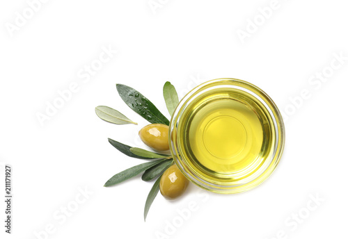 Little bowl with oil, ripe olives and leaves on white background