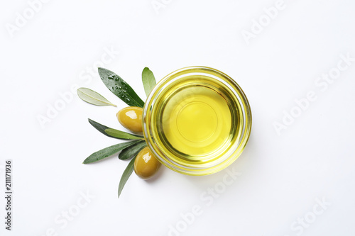 Fototapeta Little bowl with oil, ripe olives and leaves on white background
