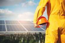 Clean Energy Concept.Electrical Worker Or Engineer Holding Safety Hat Stand At Solar Panel Background.Foreman Wearing Orange Safety Suit And Looking At Power Plant.