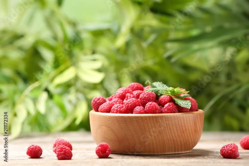Fototapeta Bowl with ripe aromatic raspberries on table against blurred background obraz na płótnie