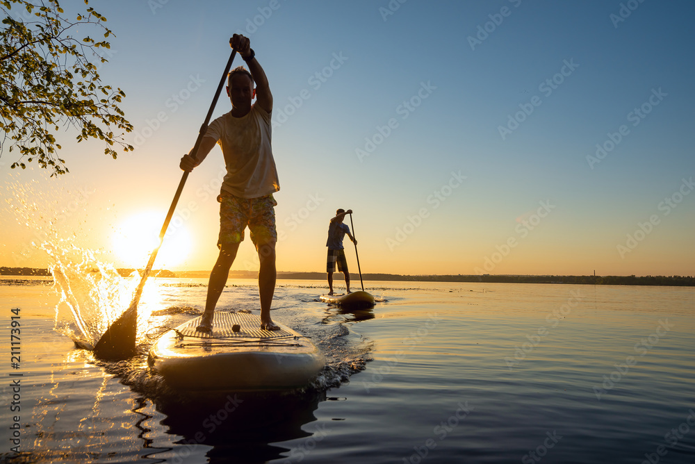 Fototapety, obrazy: Men, friends sail on a SUP boards in a rays of rising sun