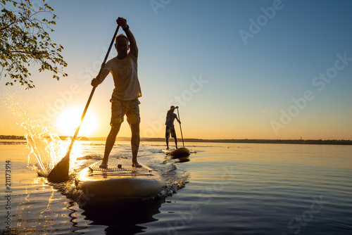 Men, friends sail on a SUP boards in a rays of rising sun