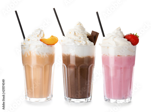Glasses with delicious milk shakes on white background