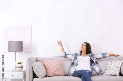 Fototapeta Young woman switching on air conditioner while sitting on sofa near white wall