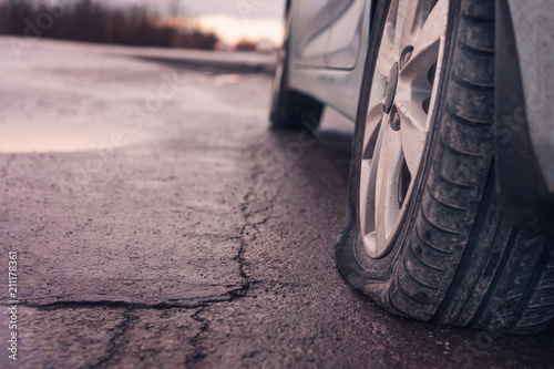Fotografiet  Flat tyre on road. Car tire leak because of nail pounding. Toned