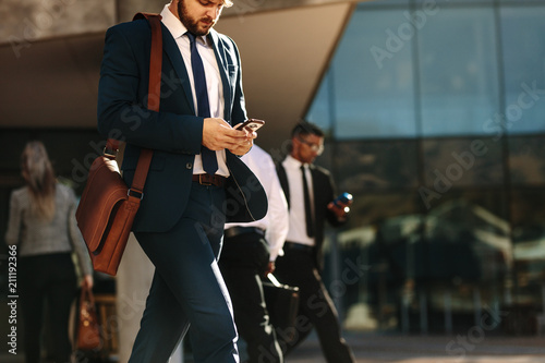 fototapeta na lodówkę Business people using mobile phone while walking on street to of