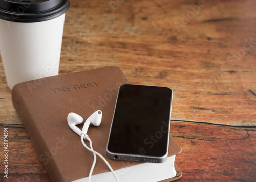 Physical Bible and a Smart Phone with Earphones on a Wood Table
