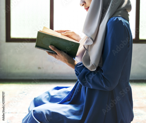 Muslim woman reading from the quran Wall mural