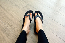 Black Flip Flops Isolated For Fashionable. Close Up Of Legs Woman. Top View. Woman Wear Black Footwear, Sandals On Wooden Background