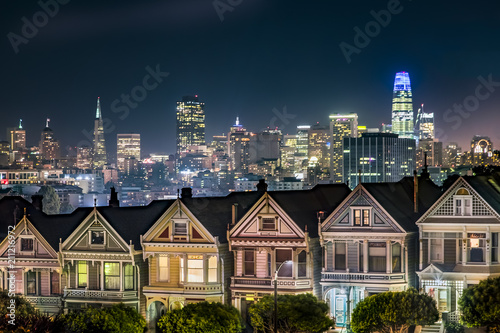 Photo Backed by the night skyline of the city of San Francisco, California, the Victorian era houses near Alamo Square Park, are painted in colors to accentuate their architectural details
