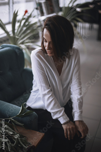 A Beautiful Girl Is Sitting On A Blue Velvet Chair And Is Resting A