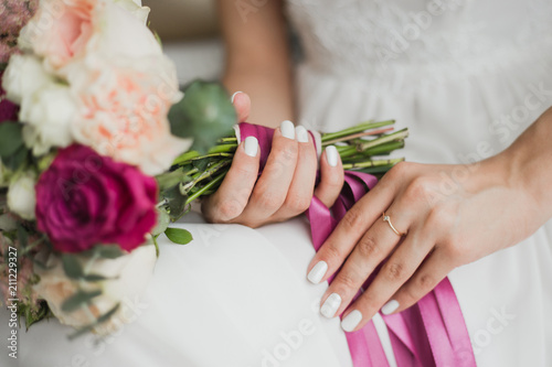 Foto Beautiful colorful wedding flowers in hands of young bride sitting alone in home interior